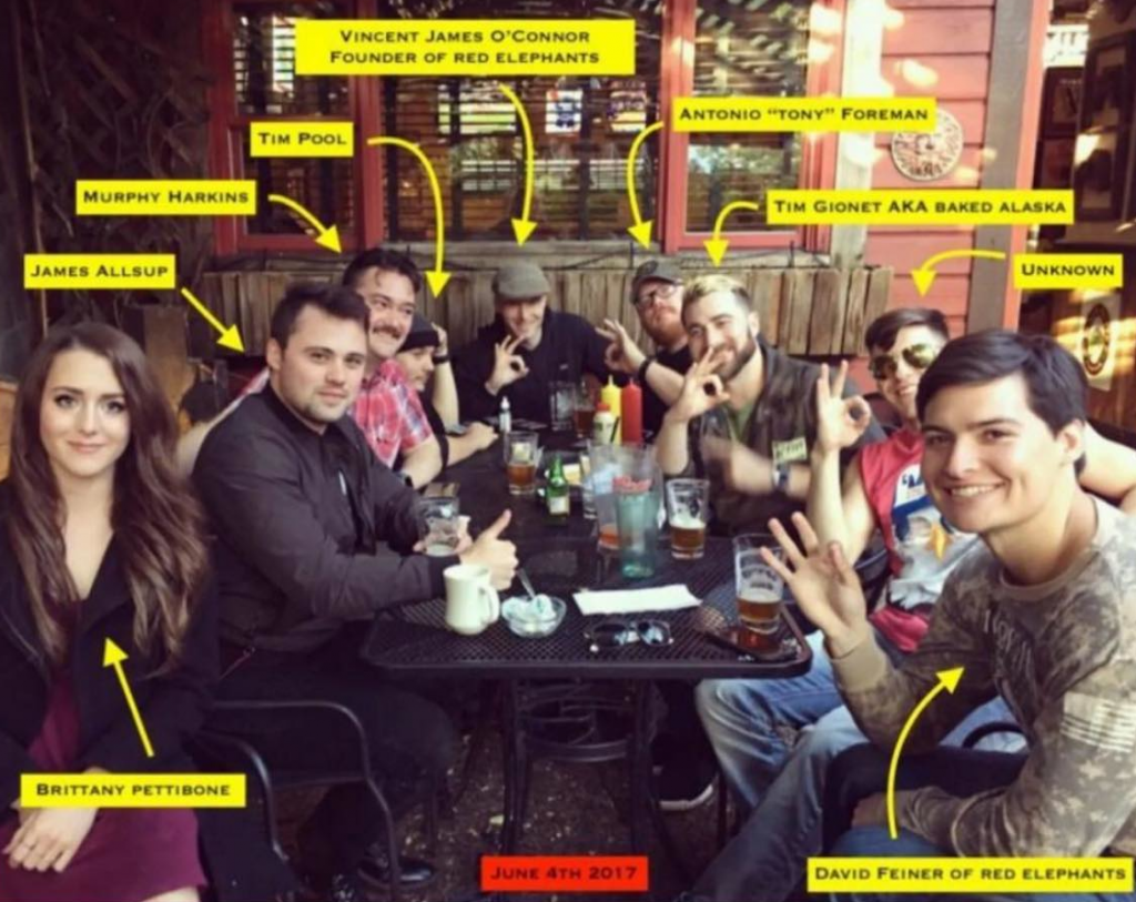 "Several individuals gathered around a table posing for a photo. Each individual has a caption with their name. From left to right, Brittany Pettibone, James Allsup, Tim Pool, Vincent James O'Connor [Foxx], Antonio ""Tony"" Foreman, Tim Gionet AKA Baked Alaska, Unknown, David Feiner."