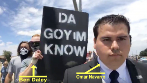 "A photograph picturing Omar Navarro (front, right, with label) standing in front of Benjamin Daley (left, rear, with label) who holds a sign reading ""Da Goyim Know"""