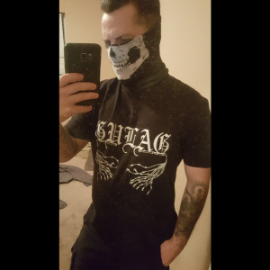 Roger Rowe posing with a neo-Nazi skull mask coverig his face.