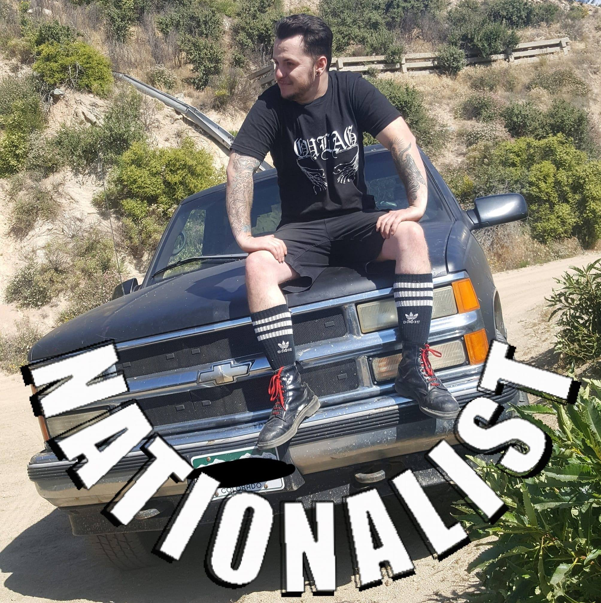 "Roger Rowe pictured sitting on the hood of a Ford truck in a desert area with the word ""Nationalist"" displayed below him."